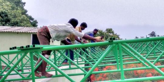 Les hommes sur le futur toit de l'école de Jalarpetai